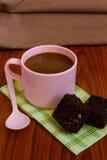 Varmt kaffe i rosa färgkopp med nisset Arkivfoton