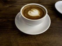 Varmt kaffe med den mjuka bubblan på gamla träbräden royaltyfri foto