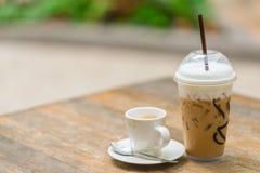 Varmt kaffe och iskaffe på den wood tabellen royaltyfri fotografi
