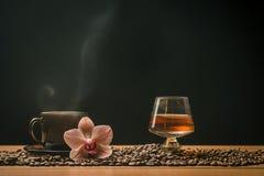 Varmt kaffe, orkidé och ett exponeringsglas av konjak Arkivbilder