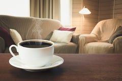 Varmt kaffe på tabletopen i modern vardagsrum i lantlig stil med stol, mjuk soffa royaltyfria foton