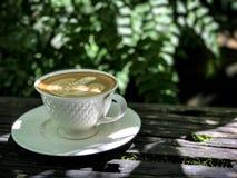 Varmt kaffe på trätabellen arkivfoton