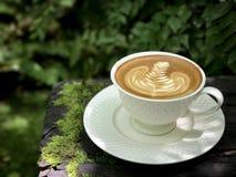 Varmt kaffe på trätabellen arkivbild