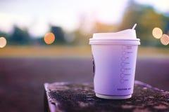 Varmt kaffe tar hem på tegelstenplattformen med brokehbakgrund Arkivfoto