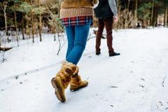 Varmt klädd flicka som når en stående man med vinterträ arkivfoto
