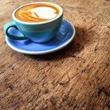 Varmt konstLattekaffe i en kopp i coffee shop på trätabellintelligens arkivfoto