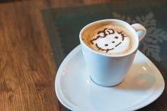 Varmt konstLattekaffe i en kopp p? tr?tabellen royaltyfria foton