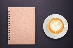 Varmt lattekaffe i den vita koppen och anteckningsboken med den tomma tomma lilla viken Arkivfoton