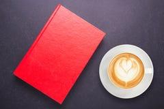 Varmt lattekaffe i den vita koppen och anteckningsboken med den tomma tomma lilla viken Royaltyfria Foton