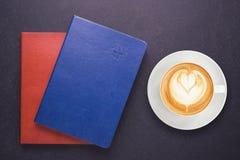 Varmt lattekaffe i den vita koppen och anteckningsboken med den tomma tomma lilla viken Arkivbilder
