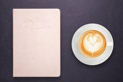 Varmt lattekaffe i den vita koppen och anteckningsboken med den tomma tomma lilla viken Arkivbild