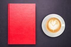 Varmt lattekaffe i den vita koppen och anteckningsboken med den tomma tomma lilla viken Fotografering för Bildbyråer