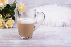Varmt lattekaffe i klar kopp och härliga gula rosor på vit träbakgrund Arkivbilder