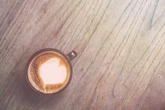 Varmt lattekaffe i svart kopp på grå trätabellbakgrund V Arkivbild