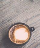 Varmt lattekaffe i svart kopp på grå trätabellbakgrund V Royaltyfria Foton