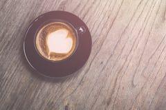 Varmt lattekaffe i svart kopp på grå trätabellbakgrund V Arkivfoto