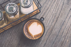 Varmt lattekaffe i svart kopp på grå trätabellbakgrund V Fotografering för Bildbyråer