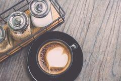 Varmt lattekaffe i svart kopp på grå trätabellbakgrund V Arkivbilder