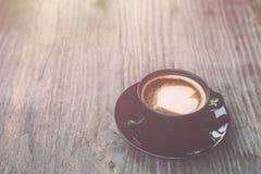 Varmt lattekaffe i svart kopp på grå trätabellbakgrund V Royaltyfria Bilder