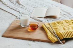 Varmt mjölka i en glass kopp och honung på träbräde Behandling av drinken folkboter i säng Stickagarn Royaltyfri Bild