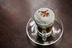 Varmt mockakaffe med mjölkar skum- och kakaopulver på en träflik Arkivbild