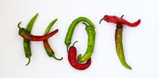 Varmt ord som göras från röd och grön peppar för varm chili på vit bakgrund Royaltyfria Bilder