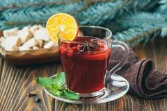 Varmt rött funderat vin på träbakgrund dekorerad blå gran förgrena sig, med julkryddor, den orange skivan, den nya mintkaramellen Royaltyfria Bilder