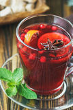 Varmt rött funderat vin på träbakgrund dekorerade med julkryddor Fotografering för Bildbyråer