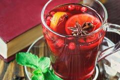Varmt rött funderat vin på träbakgrund dekorerade med julkryddor Arkivbild