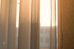 Varmt solljus som skiner till och med rena gardiner arkivbilder
