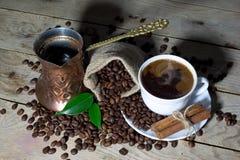 Varmt svart kaffe i kaffekruka och kopp för vitt kaffe med kanel- och kaffebönor i jutepåse på trätabellen Royaltyfri Fotografi