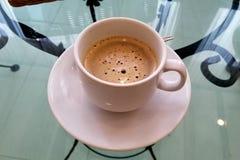 Varmt svart kaffe som förläggas i en exponeringsglastabell royaltyfria foton