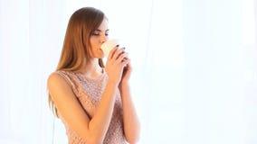 Varmt te eller kaffe för flickadrink, medan stå på fönstret arkivfilmer