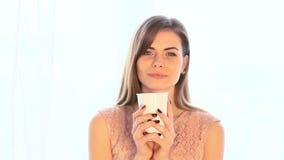 Varmt te eller kaffe för flickadrink, medan stå på fönstret stock video