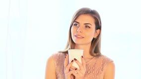 Varmt te eller kaffe för flickadrink, medan stå på fönstret lager videofilmer