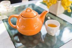 Varmt te hällde in i koppen med den orange krukan Arkivfoton