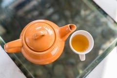 Varmt te hällde in i koppen med den orange krukan Arkivbild