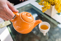 Varmt te hällde in i koppen med den orange krukan Royaltyfri Bild