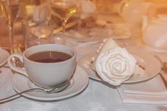 Varmt te i den glass genomskinliga koppen och ett stycke av kakan dekorerade med en ros på restaurangen Royaltyfria Foton