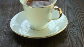 Varmt te i en porslinkopp på tefatet arkivfilmer
