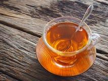 Varmt te i ett exponeringsglas på en trätabell Arkivfoton