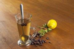 Varmt te med citronen och röd pil i tabellen Hem- behandling för förkylningar och influensa royaltyfri bild