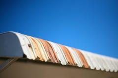 Varmt tenn- tak, skalning och rosta under en klar sommarhimmel Arkivfoto
