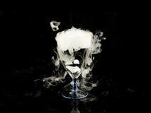 Varmvatten i vinexponeringsglas med rök på svart bakgrund Arkivbilder