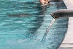 Varmvatten som flödar in i en pöl, brunnsortbakgrund Arkivbild