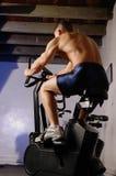 Varón en la bici de ejercicio Fotografía de archivo libre de regalías