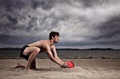 Varón fuerte con la bola roja en la playa Fotos de archivo