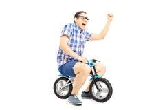 Varón joven emocionado que monta una pequeña bicicleta y que gesticula happines Foto de archivo libre de regalías