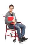 Varón sonriente en cuadernos de una explotación agrícola del sillón de ruedas Foto de archivo libre de regalías