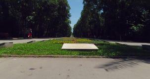 Varna Bulgaria, vista aérea del parque del jardín del mar con las flores coloridas y el hombre de funcionamiento metrajes